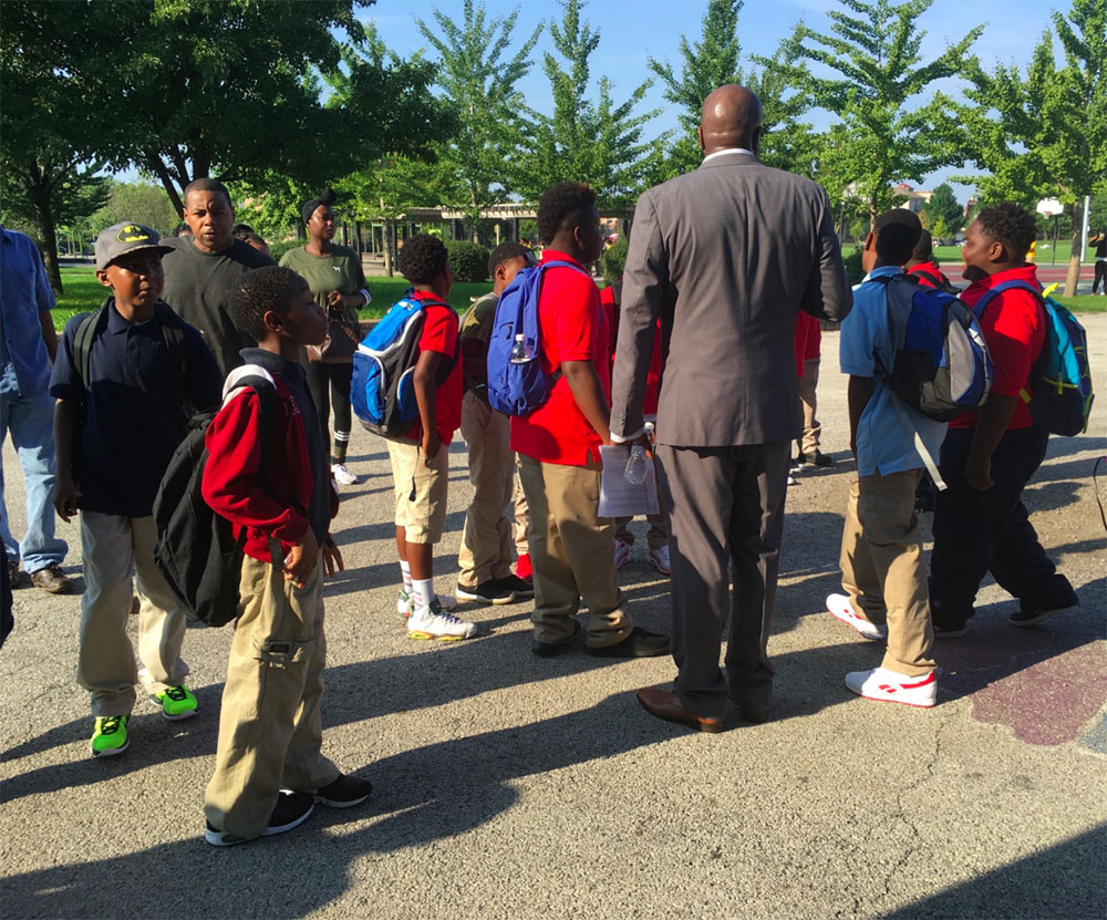 Administrator at Carter G. Woodson Elementary greeting students as they enter school building